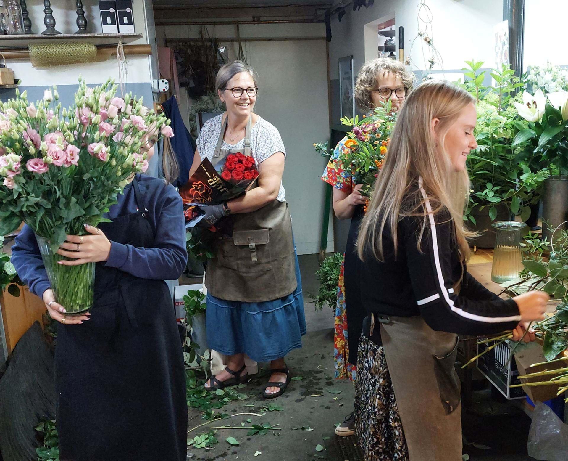 Hænder der holder mobiltelefon og tager billede af blomster